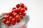 Cherry Tomatoes Tumbling Into Metal Colander — Stock Photo