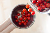 Cherry Tomatoes Tumbling From Metal Colander Into Metal Pan — Stock Photo