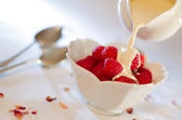 Cream Pouring From a Jug Over Fresh Raspberries — Stock Photo