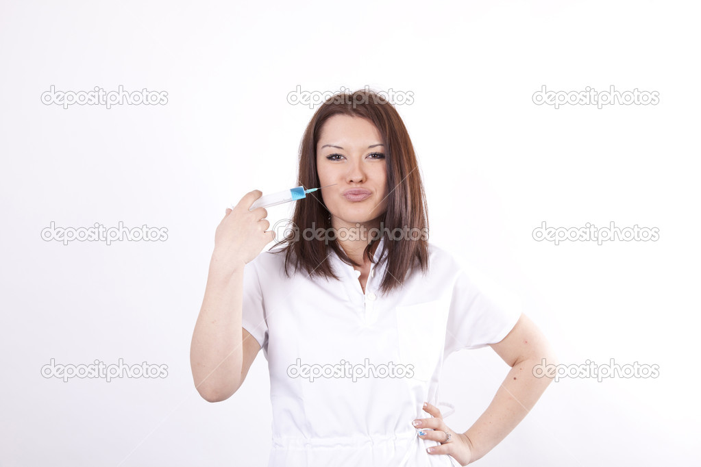 Young attractive female doctor pointing syringe to her cheeks and lips.  Stock Photo #11509733