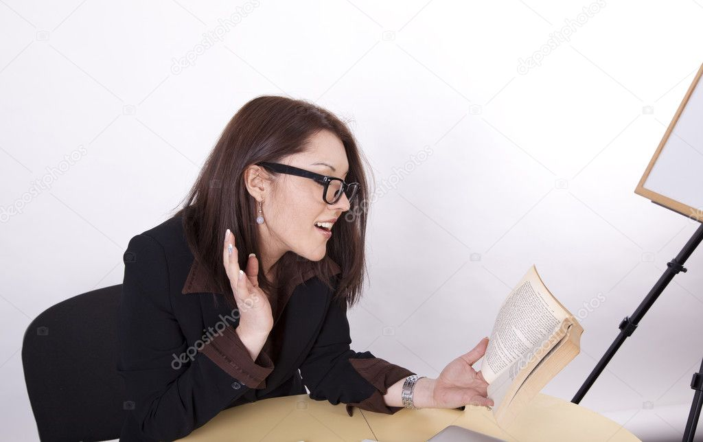 Young beautiful surprised woman at the office reading a book. — Stock Photo #11516849
