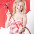 Young attractive woman with red umbrella and basket — Stock Photo
