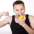 Young attractive male eating orange — Stock Photo