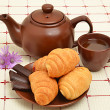 Brown teapot, cup and sauser with croissant — Stock Photo