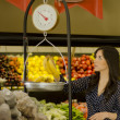 Young beautiful woman weighing fruits on a scale in a supermarket — Stock Photo #11420362