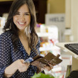 Cute young woman paying at the cash register in a supermarket - Stok fotoğraf