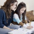 Young beautiful mother coloring a book with her daughter — Stock Photo #11420497