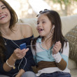 Young beautiful mother listening to music with her daughter — Stock Photo #11420503