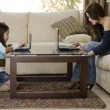 Young mother and daughter using their laptops in the living room - Stock Photo