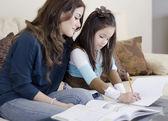 Joven hermosa madre un libro para colorear con su hija — Foto de Stock