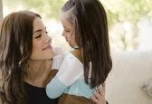 Genç güzel anne ve kızı birbirine bakarak ve gülümseyerek — Stok fotoğraf