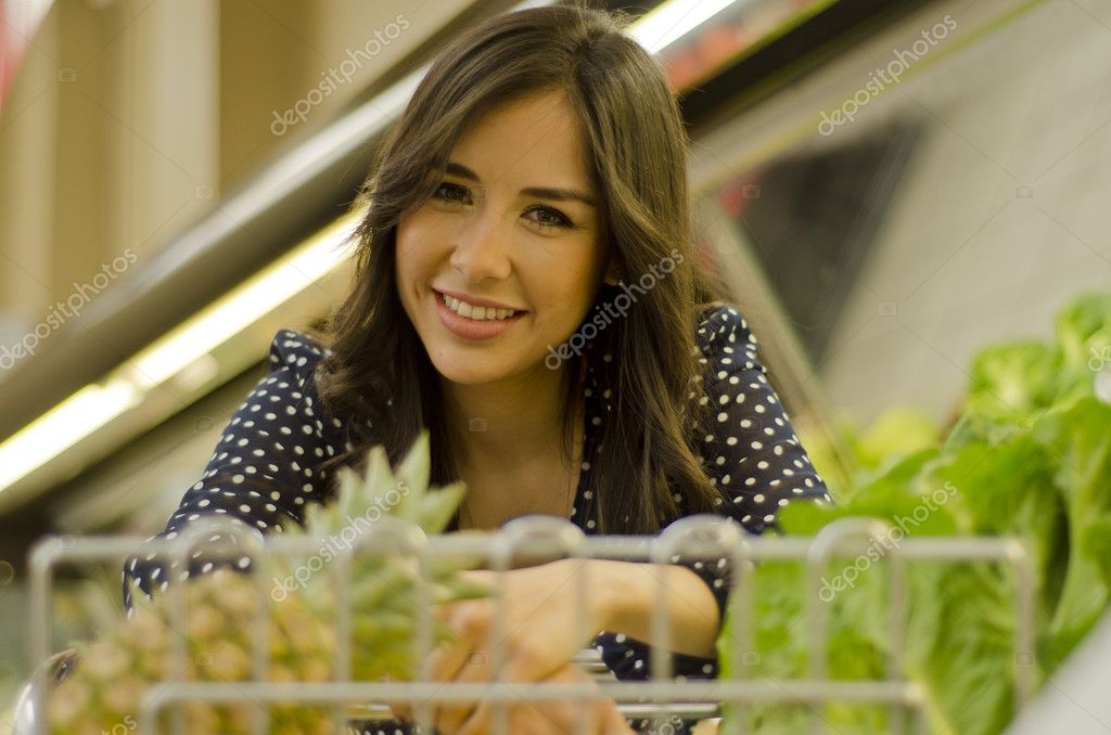 Young cute woman shopping with a cart in a grocery store — Stock Photo #11420425