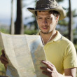 Young man finding his way with a map — Stock Photo