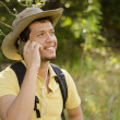 Young man talking on the phone on a hiking trip — Stock Photo
