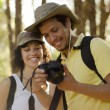Cute young couple looking at pictures of their hiking trip - Stock Photo