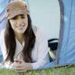 Young beautiful woman smiling outside of a tent on a camping trip — Stock Photo