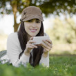 Young beautiful woman sending a text on her cell phone while resting on hiking trip — Stock Photo