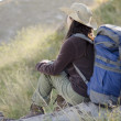 Young hiker with backpack taking a break and admiring the view - Stock Photo