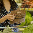Young woman opening wallet at the supermarket — Stock Photo