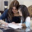 Young beautiful mother coloring a book with her daughter — Stock Photo #11446487