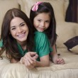 Portrait of young mother and her daughter having fun in the bedroom — Stock Photo #11446524