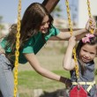 Stock Photo: Young mother pushing daughter on the swing