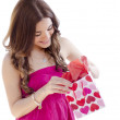 Cute young woman smiling and opening a gift - Stockfoto