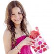 Cute young woman smiling and opening a gift - Stock Photo