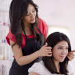 Young female hairdresser showing final result to customer — Stock Photo