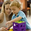 Cute boy and mother playing with a puzzle  — Stock Photo