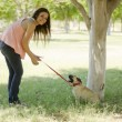 Cute young woman walking her dog at a park — Stock Photo #11447067