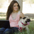 Cute young woman spending time with her dog at the park — Stock Photo