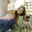 Stock Photo: Young beautiful womtaking picture with her dog at park