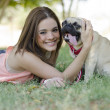 Cute young woman spending some time with her pug dog at the park - Stock Photo