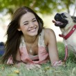 Cute young woman spending some time with her pug dog at the park — Стоковое фото #11447090