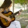 Cute young woman playing some music at the park - Stock Photo