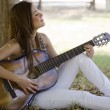 Cute young womplaying guitar at park — Stock Photo #11447124