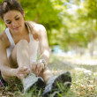 Cute young woman tying her shoelaces before running - Stock Photo