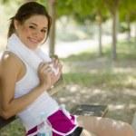 Милая девушка, принимая перерыва после запуска в парке — Стоковое фото