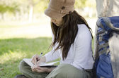 Young beautiful woman writing on a journal about her hiking trip — Stock Photo