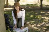 Ung kvinna söker till en karta på marken och leende på fotvandring resa — Stockfoto