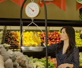 Young beautiful woman weighing fruits on a scale in a supermarket — ストック写真