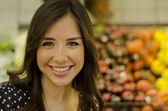 Jovem mulher bonita sorrindo em um supermercado — Foto Stock