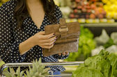 Young woman opening wallet at the supermarket — Stok fotoğraf
