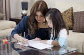 Young beautiful mother coloring a book with her daughter — Stock Photo