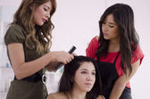 Female hairstylist teaching an apprentice — Stock Photo