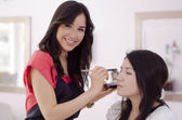 Female makeup artist applying makeup on a client — Stock Photo