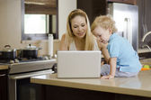 Young beautiful mother showing something to her son in her laptop — Stock Photo