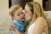 Beautiful young mother kissing her son on the cheek — Stock Photo