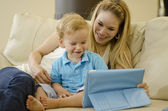Beautiful young mother playing with her son and a tablet — Stock Photo